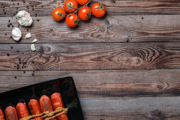 나무 테이블에 검은 접시에 구운 소시지. 텍스트, 로고 등을 위한 빈 공간이 있는 위쪽 보기