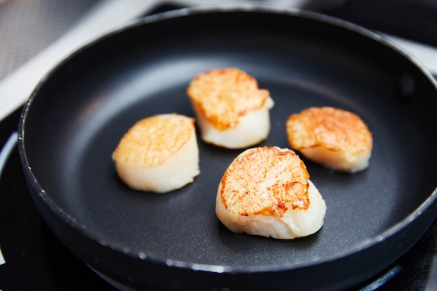 Roasted scallops fried in a black pan