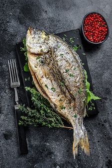 Roasted sea bream  fish with herbs on a cutting board. black background. top view.