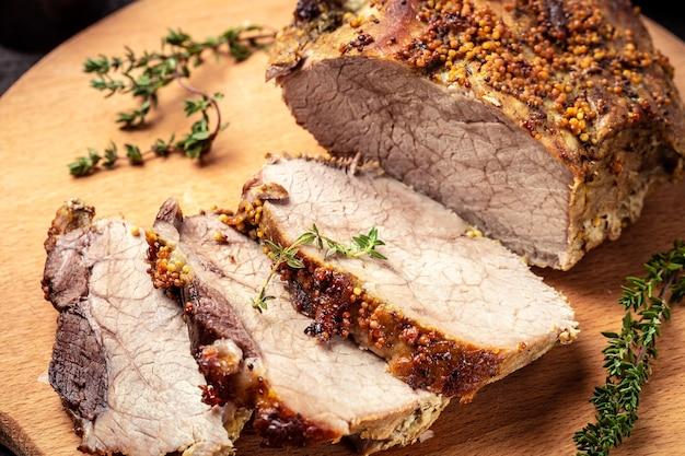 Жареная лопатка на разделочной доске, жареная рождественская ветчина из индейки. большой кусок запеченной свинины с горчицей,