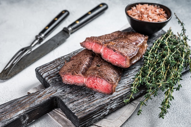 Жареный лопатка или стейки из говядины на деревянной доске. вид сверху.