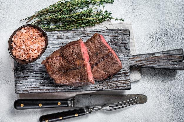 구운 숄더 탑 블레이드 또는 나무 판자에 평평한 철 쇠고기 고기 스테이크. 흰 바탕. 평면도.