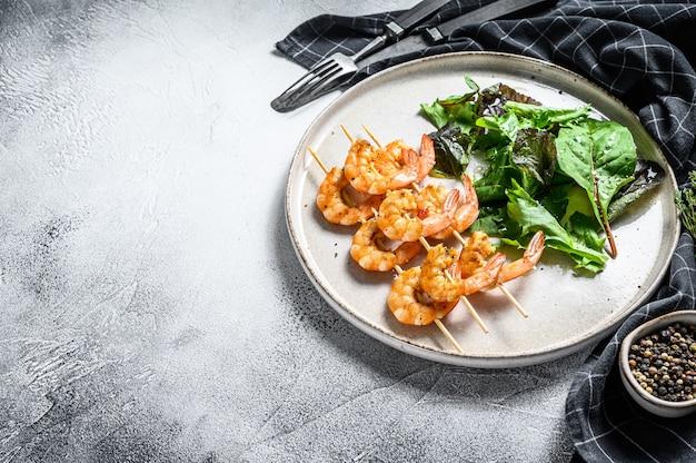 Жареные креветки, креветки на шпажках с салатом из шпината. вид сверху. копировать пространство