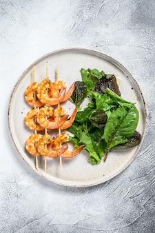 Жареные креветки, креветки на шпажках с салатом из шпината