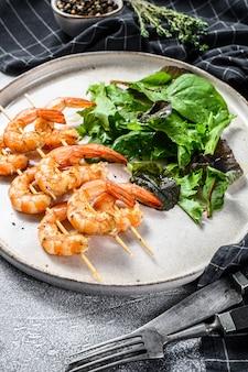 Жареные креветки, креветки на шпажках с салатом из шпината.