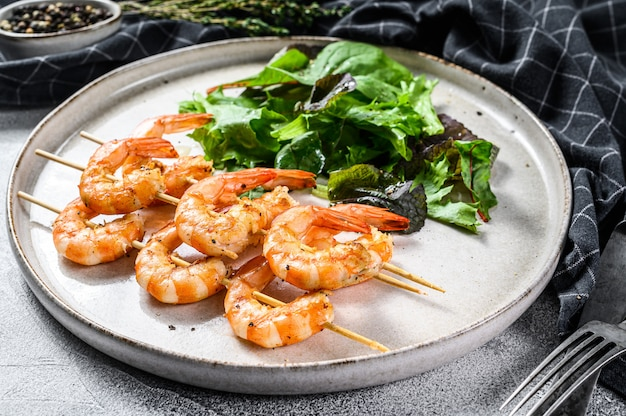 Roasted shrimps, prawns on skewers with spinach salad.
