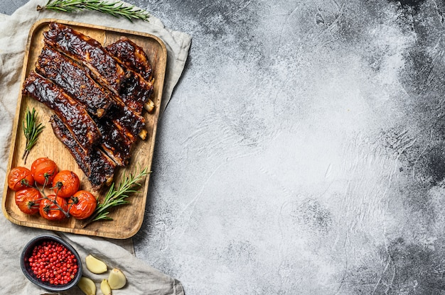 Roasted sliced barbecue pork ribs. grilled meat. gray background. top view. space for text