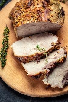 Жареный нарезанный рождественский окорок из индейки. большой кусок запеченной свинины с горчицей на разделочной доске. баннер, меню рецепт вертикальное изображение, вид сверху.