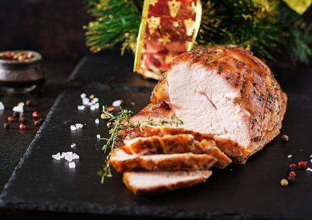 Roasted sliced christmas ham of turkey on dark rustic surface. festival food.