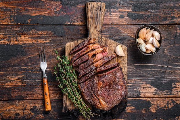 Roasted and sliced rib eye beef meat steak on a wooden cutting board with thyme.