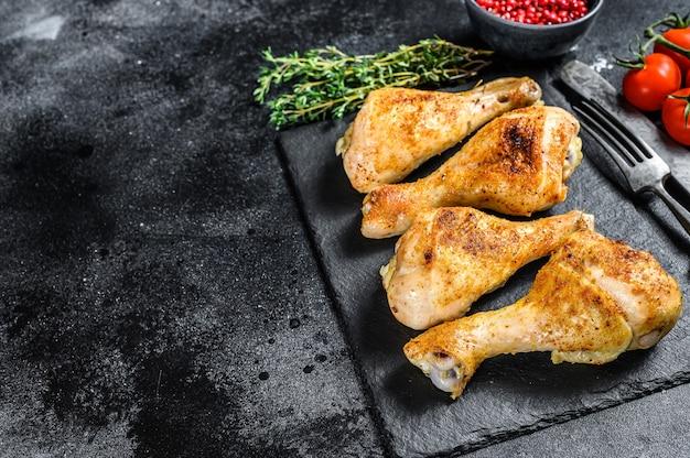 スパイシーな鶏のモモ肉のロースト、スパイスとハーブのすね肉。黒の背景。上面図。スペースをコピーします。