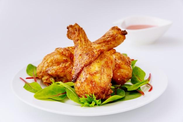 흰색 테이블에 샐러드와 구운 된 매운 치킨 드럼 스틱. 확대.