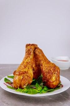 Жареные острые куриные голени с салатом на белой поверхности