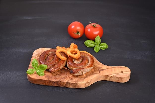 Жареная пряная спиральная колбаса с листьями базилика и жареным картофелем