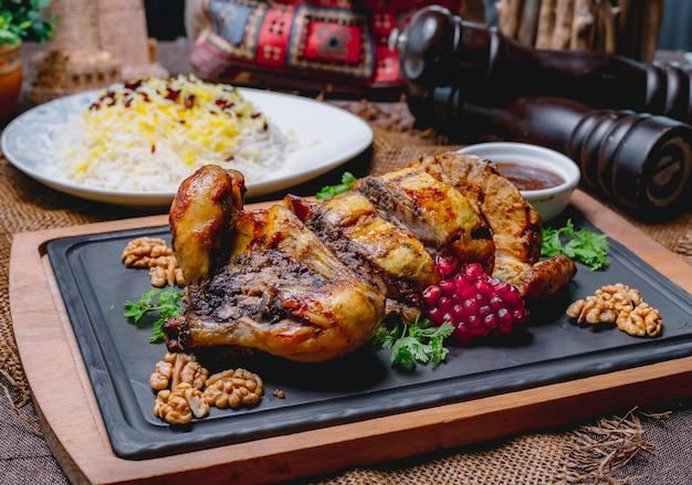 Pollo ripieno arrosto decorato con melograno e noci su un bordo nero e riso in un piatto bianco su un tavolo di legno