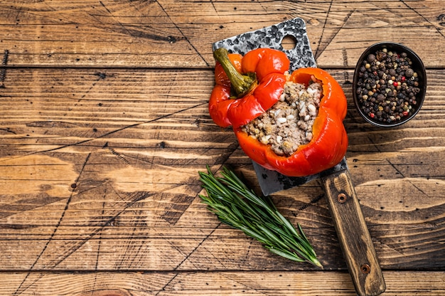 Roasted sweet bell pepper with meat, rice and vegetables. wooden background. top view. copy space.
