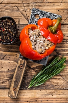 Roasted sweet bell pepper with meat, rice and vegetables. wooden background. top view.