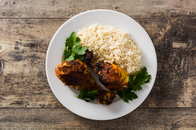 Roasted tandoori chicken with basmati rice in plate on wooden table. top view