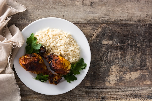 Roasted tandoori chicken with basmati rice in plate on wooden table. top view.