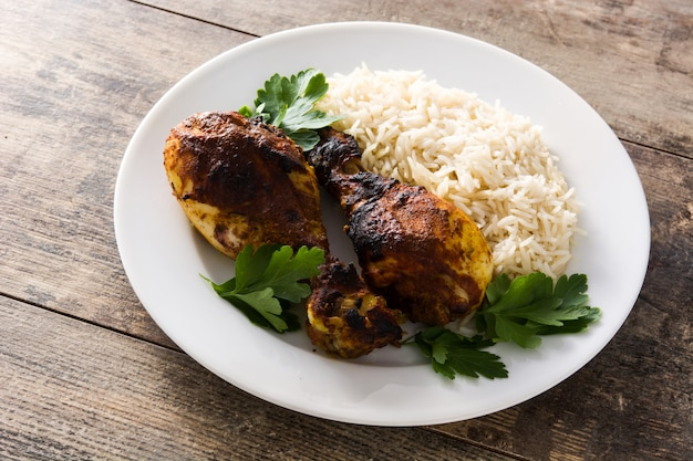 Roasted tandoori chicken with basmati rice in plate on wooden table.