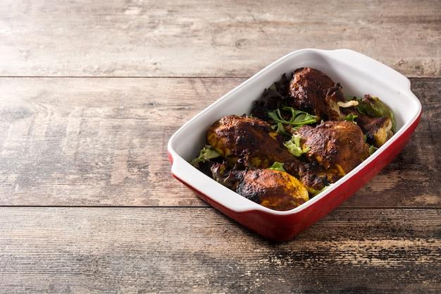 Roasted tandoori chicken on wooden table