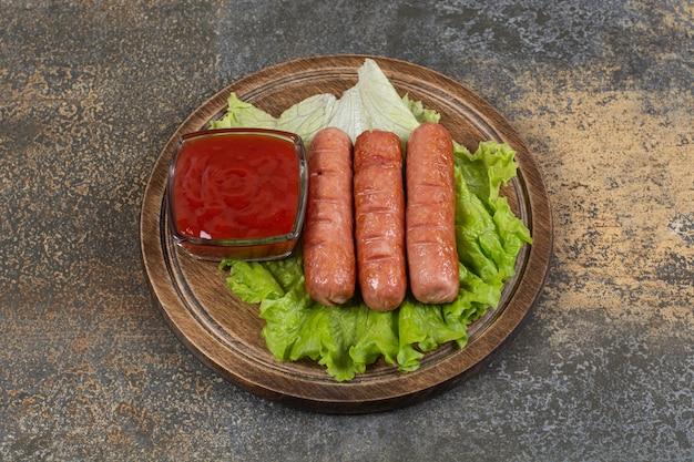 Gustose salsicce arrostite e ketchup su tavola di legno.