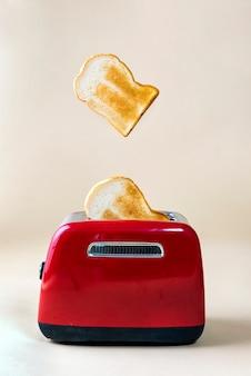빨간 토스터에서 튀어나온 구운 토스트 빵