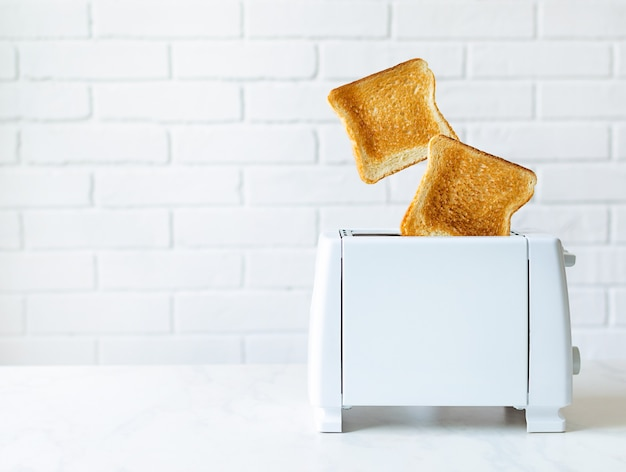 Roasted toast bread popping up of toaster with white brickwall.