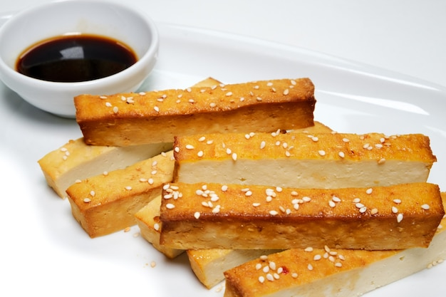 ロースト豆腐-人気のベジタリアンチーズ、白いプレート。