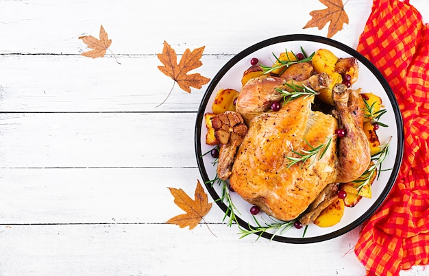 Roasted turkey garnished with cranberries on a rustic style table decorated  autumn leaf. thanksgiving day. baked chicken. top view