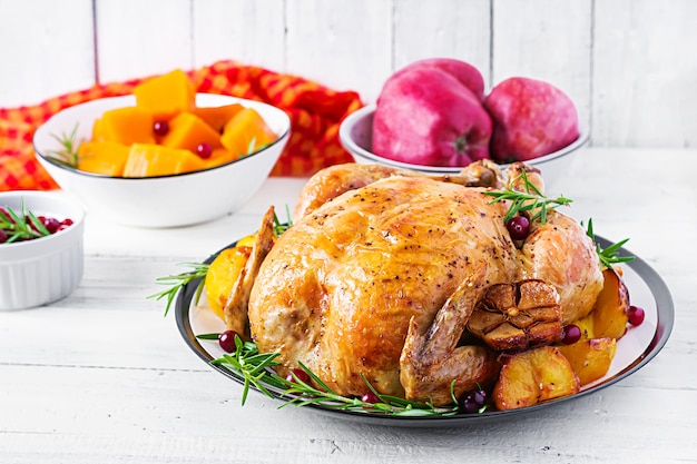 Roasted turkey garnished with cranberries on a rustic style table decorated  autumn leaf. thanksgiving day. baked chicken.