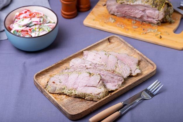 나무 판자에 구운 칠면조 허벅지를 조각으로 자릅니다. 배경에는 야채 샐러드 한 그릇과 칠면조가 있습니다. 확대.