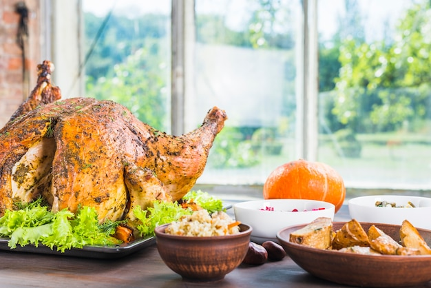 Roasted turkey with dishes on table