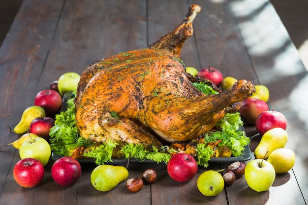 Roasted turkey with fruits on table