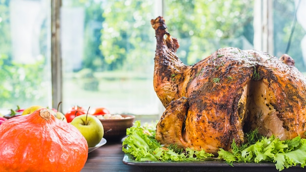Roasted turkey with pumpkin on table