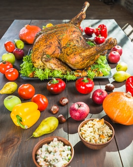 Roasted turkey with vegetables on wooden table