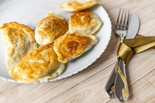 나무 배경에 칼 주위에 실크 활과 하얀 접시에 구운 varenyky 만두