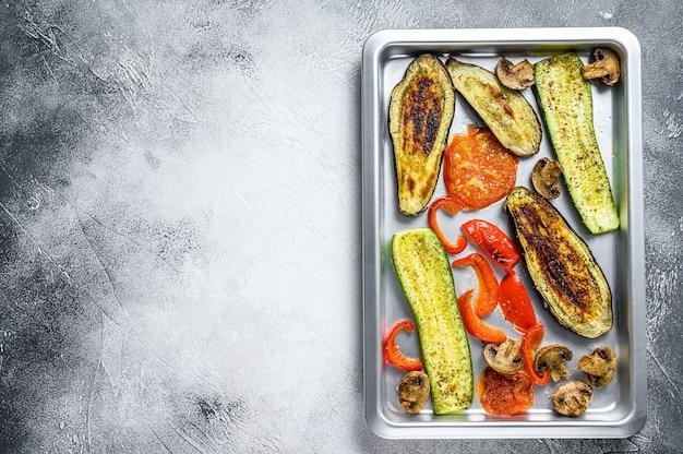 Жареные овощи на противне. белый фон. вид сверху. скопируйте пространство.