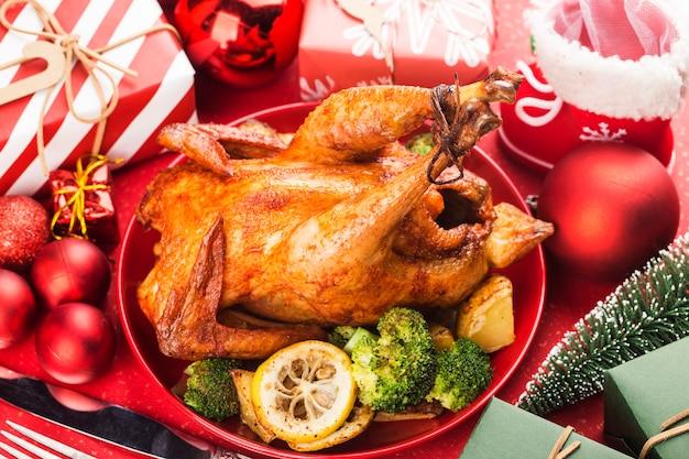 Жареный цыпленок целиком с рождественским украшением.