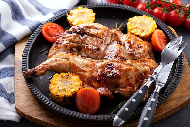 Roasted whole  chicken  with corn and tomatoes on frying pan.
