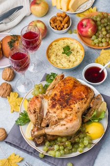 Roasted whole chicken with lemon and grapes on gray light surface