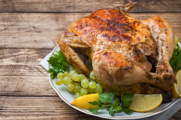 Roasted whole chicken with lemon and grapes on wooden table