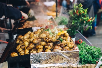 Roasted whole potatoes with vegetables at a food market