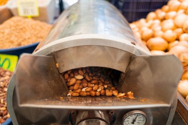 땅콩 굽기 및 데치기. 기계에서 땅콩을 껍질을 벗기는 과정.