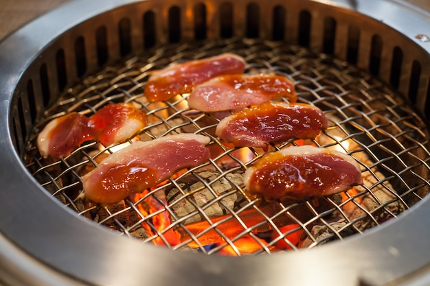 Roasting duck meat food on glowing and flaming hot wood charcoal lump