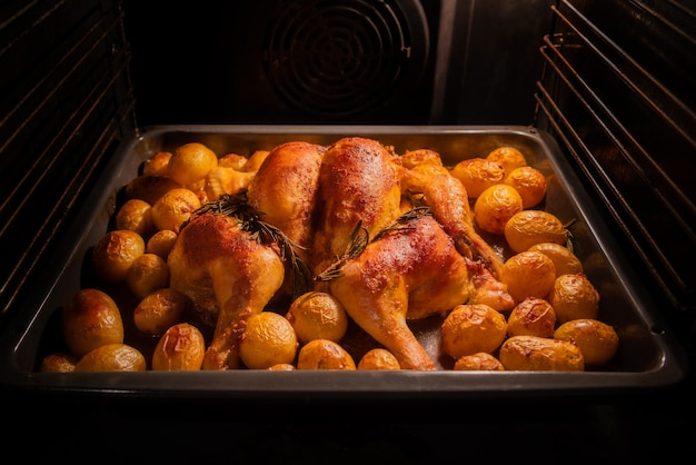 Roasting whole chicken and potatoes in the oven.