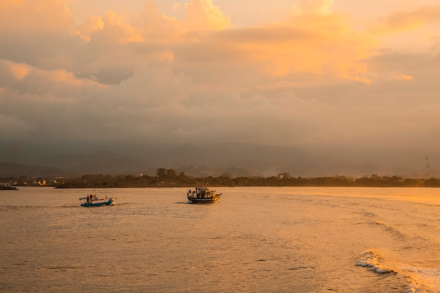 Roatan, honduras : fishing boats in the sea at sunset seen from the ferry heading to roatan island