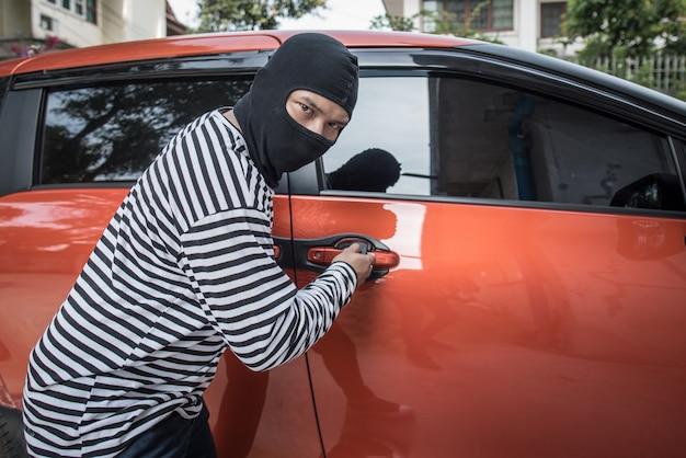 Грабитель и угонщик в маске открывают дверь машины и угоняют машину. Premium Фотографии