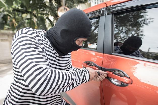 Грабитель и угонщик в маске открывают дверь машины и угоняют машину.