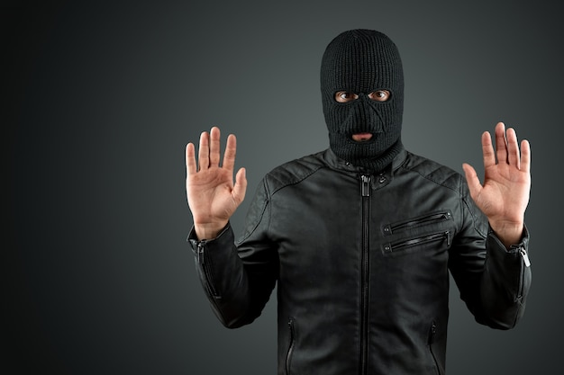 Robber in a balaclava surrendering raise his hands on a black background